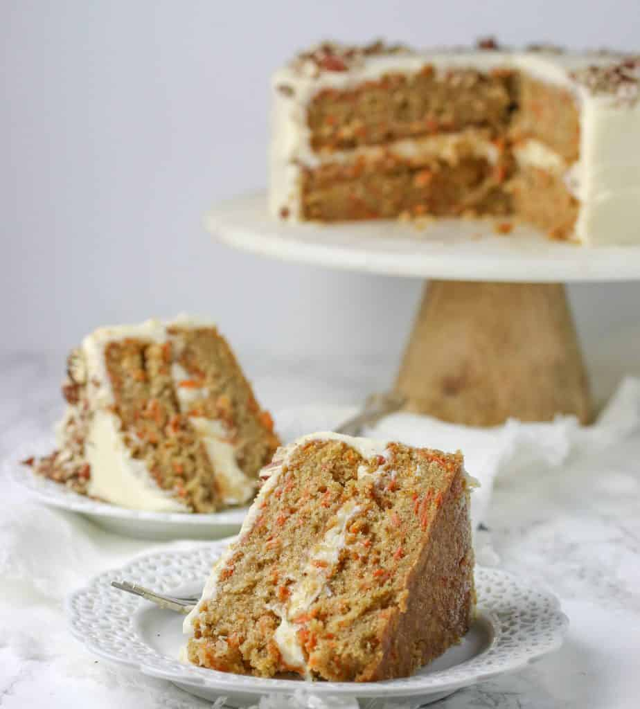 carrot layer cake slices on plate with a whole cake in the background