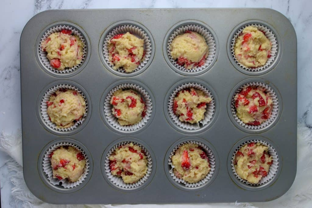 strawberry muffin batter scooped into muffin liners