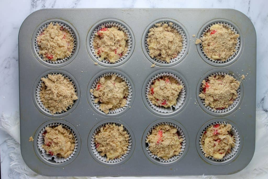 strawberry muffin batter in muffin tin with streusel on top