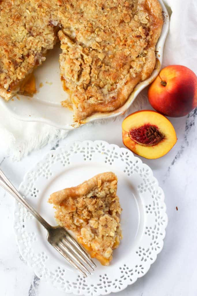 slice of nectarine pie on a plate next to the whole pie in a plate