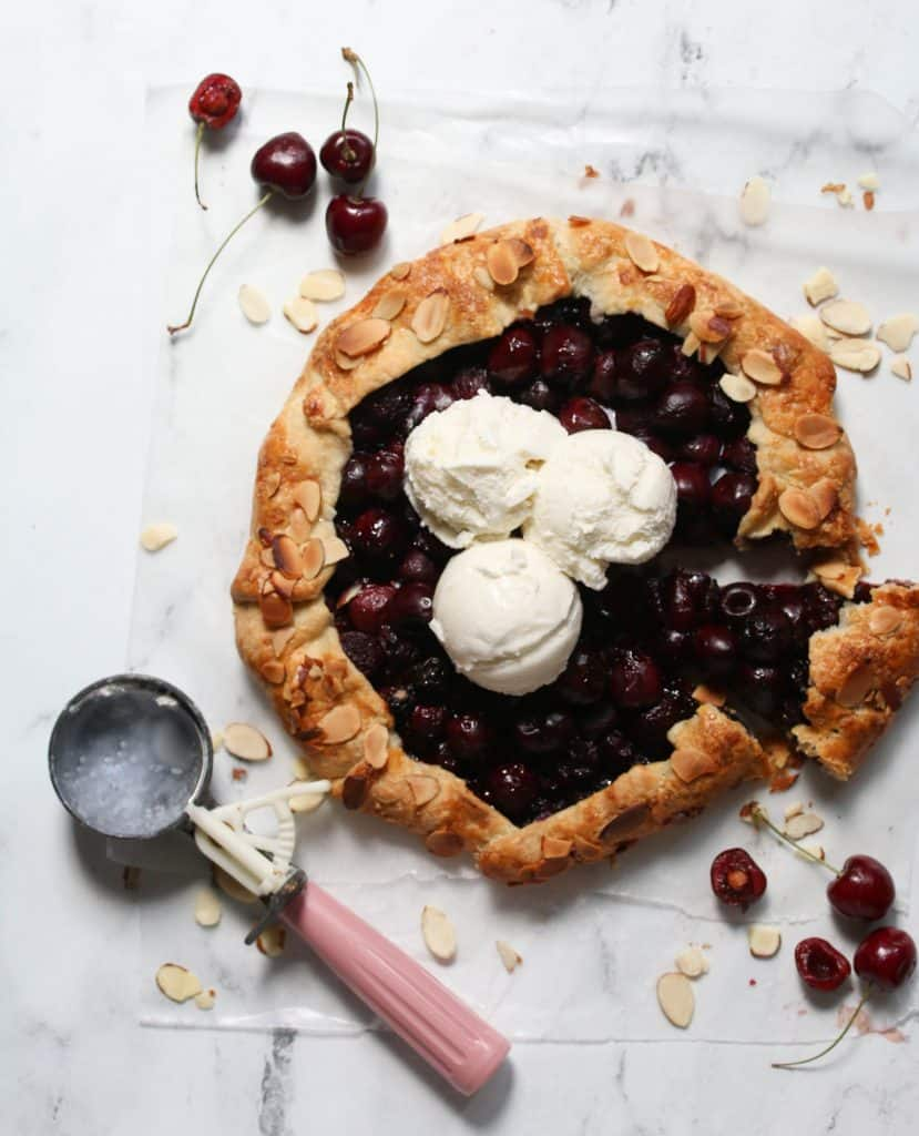 cherry crostata topped with three scoops of vanilla ice-cream and a ice-cream scoop next to it