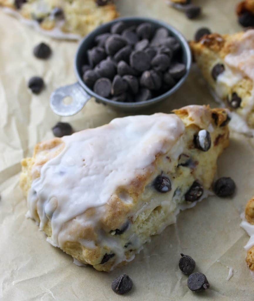 chocolate chip scone with glaze and a cup of chocolate chips