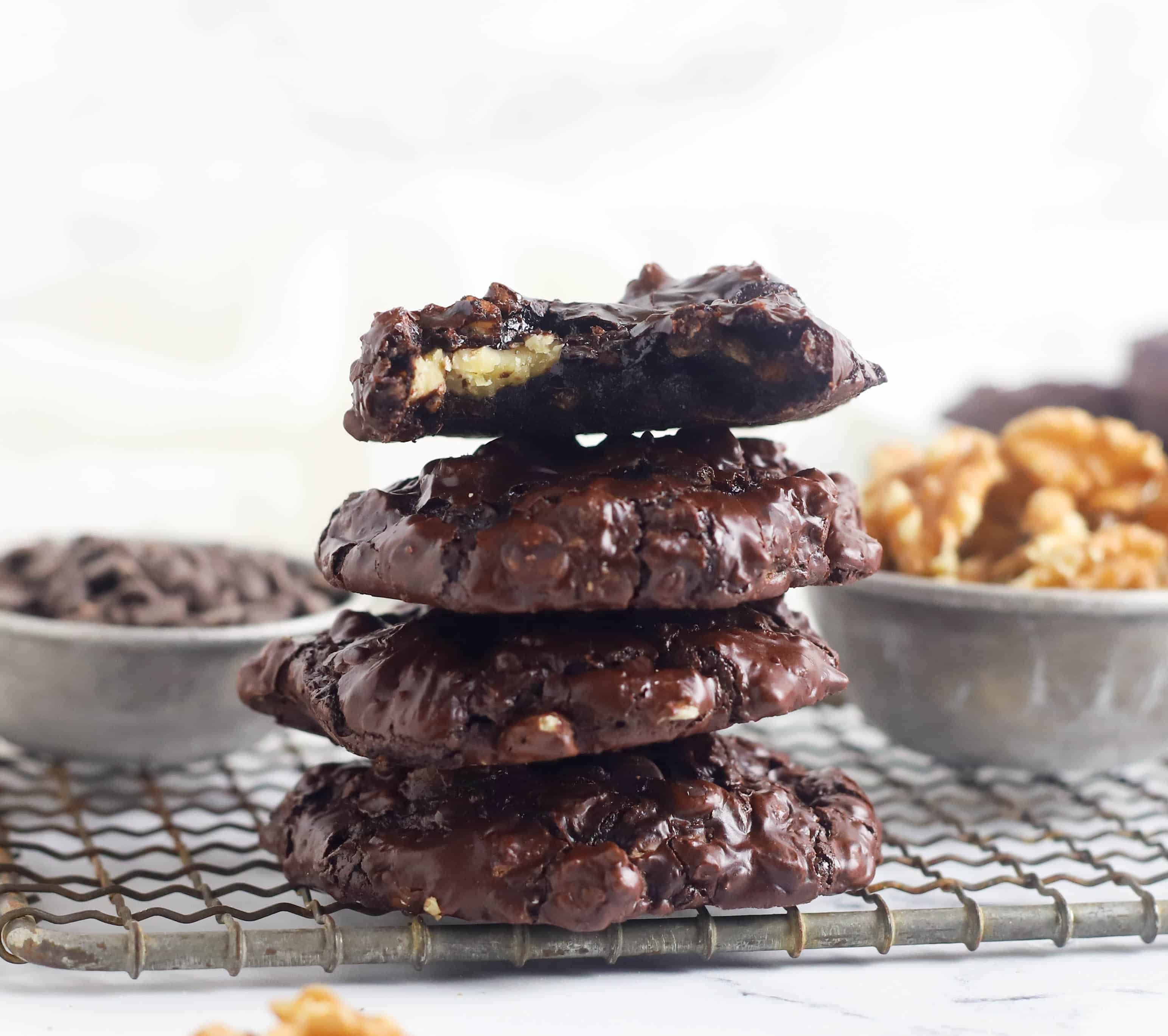 four chocolate walnut cookies stacked on top of each other