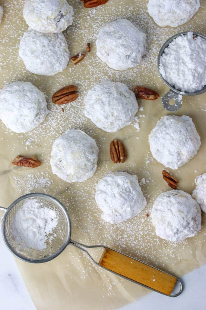 russian tea cakes on parchment with pecans