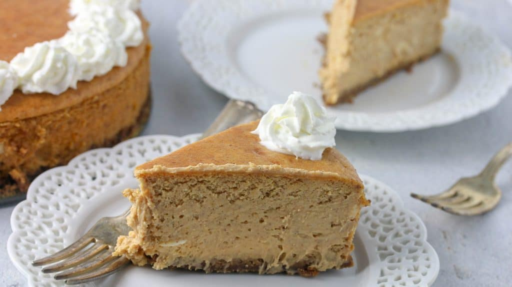 slice of pumpkin cheesecake on a plate with whipped cream