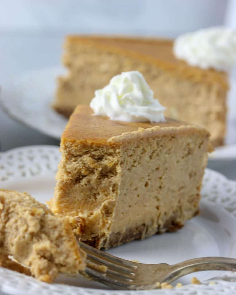 slice of pumpkin cheesecake with a fork on a plate