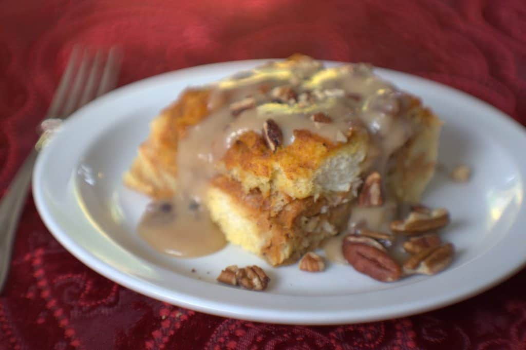 slice of pumpkin praline bread pudding on a plate with pecans