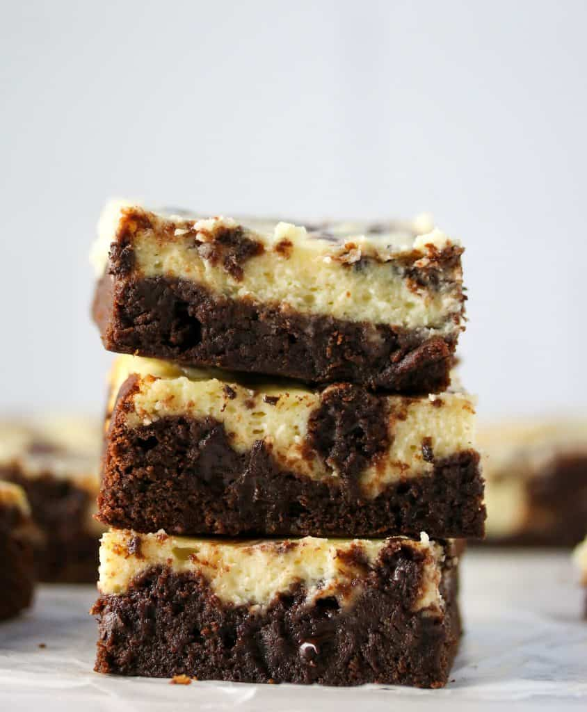 three cheesecake brownies stacked on top of each other