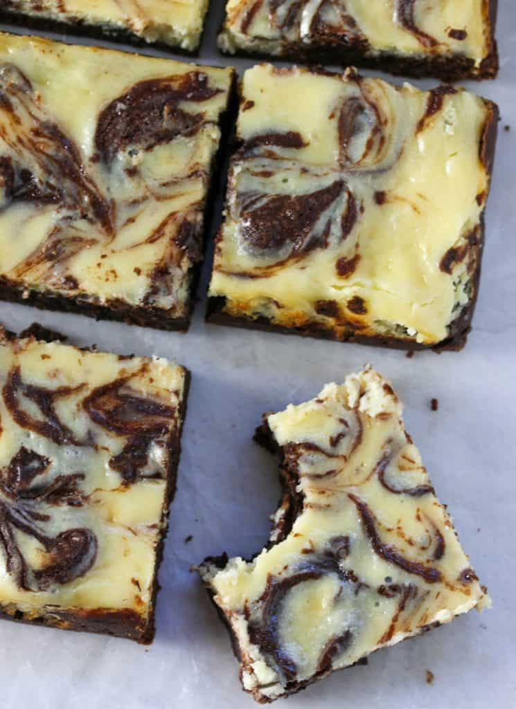 cheesecake brownies cut into squares with one that has a bite taken out of it