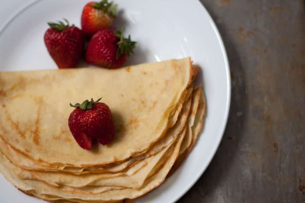 stack of crepes with strawberries on a plate