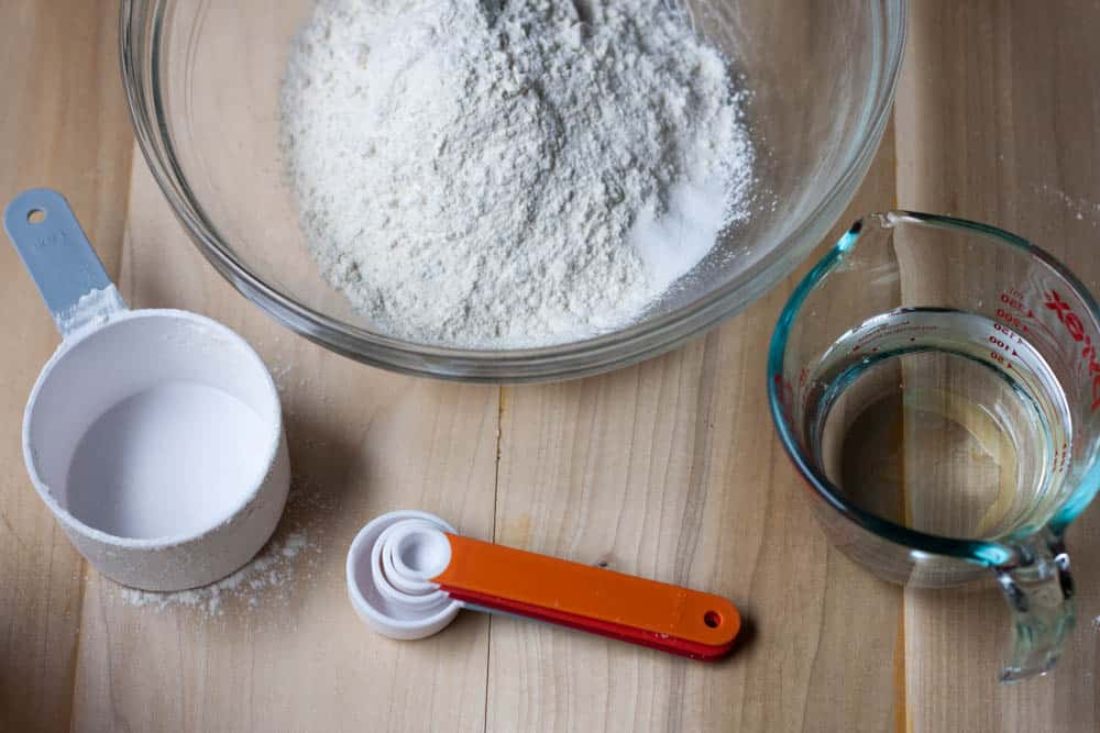 bowl of flour, cup of water, and measuring cups