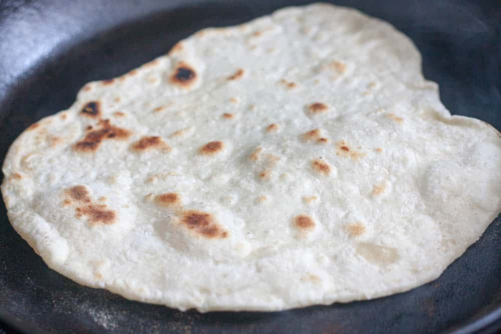 flour tortillas cooking in a cast iron