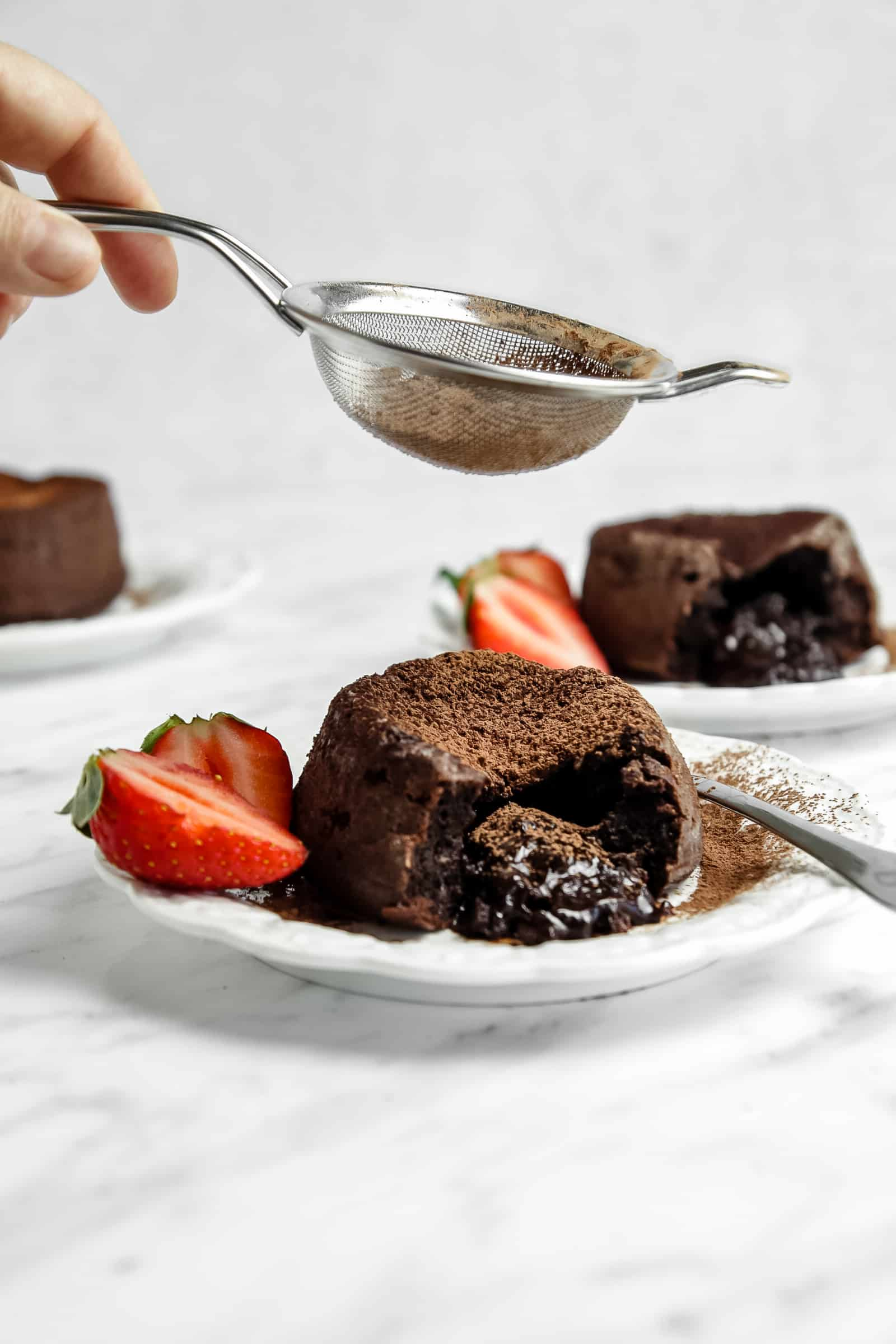 molten chocolate cake being dusted with cocoa powder