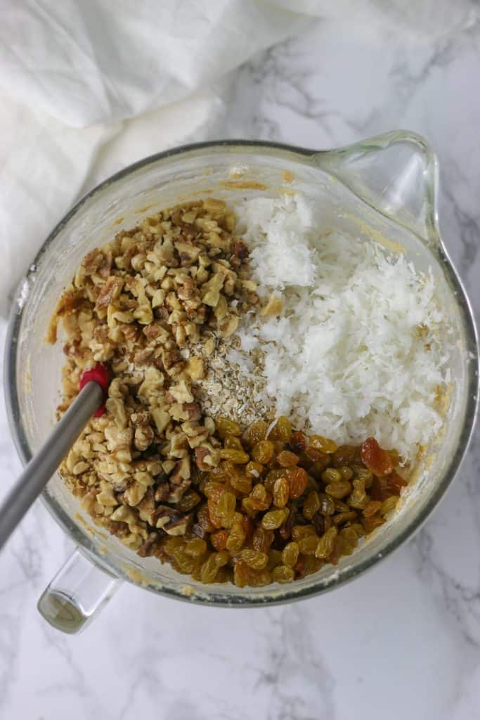 walnuts, coconut, and raisins in carrot cookie dough bowl