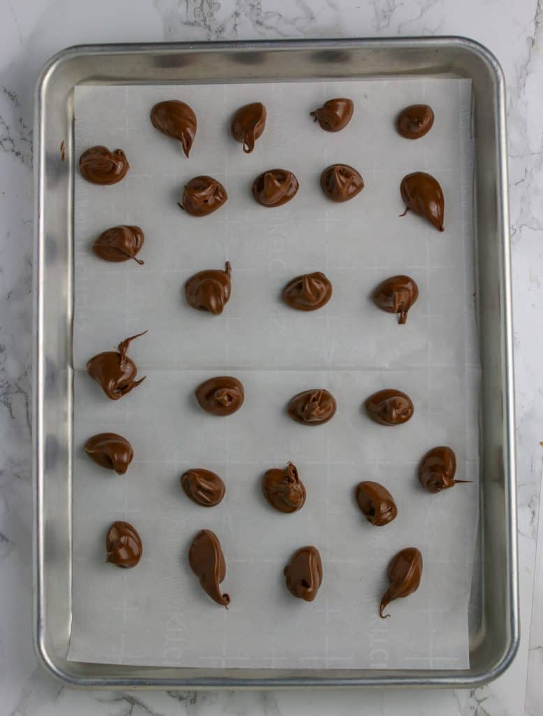 dollops of nutella piped onto a cookie sheet