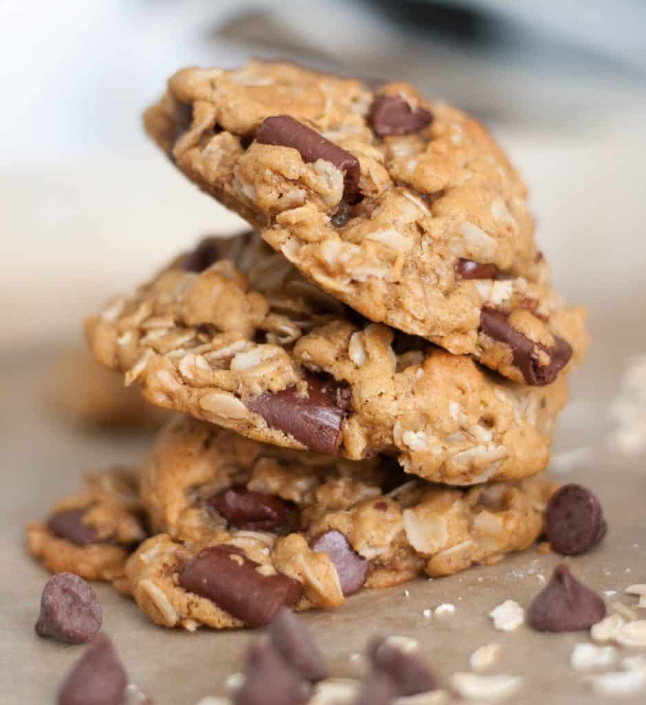 three flourless oatmeal cookies stacked on parchment paper