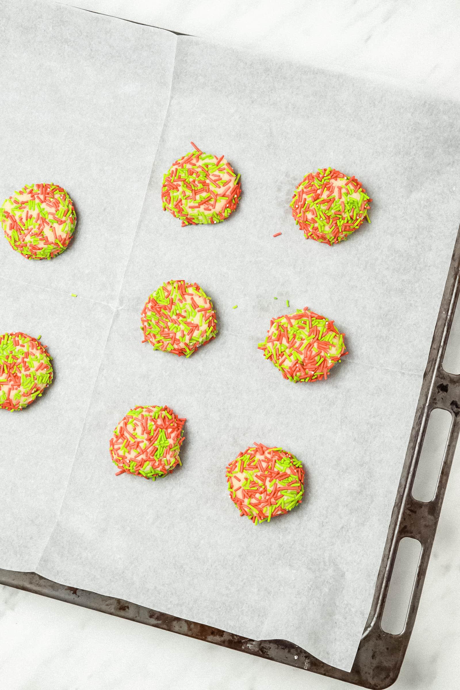 unbaked sprinkle sugar cookies on a baking sheet