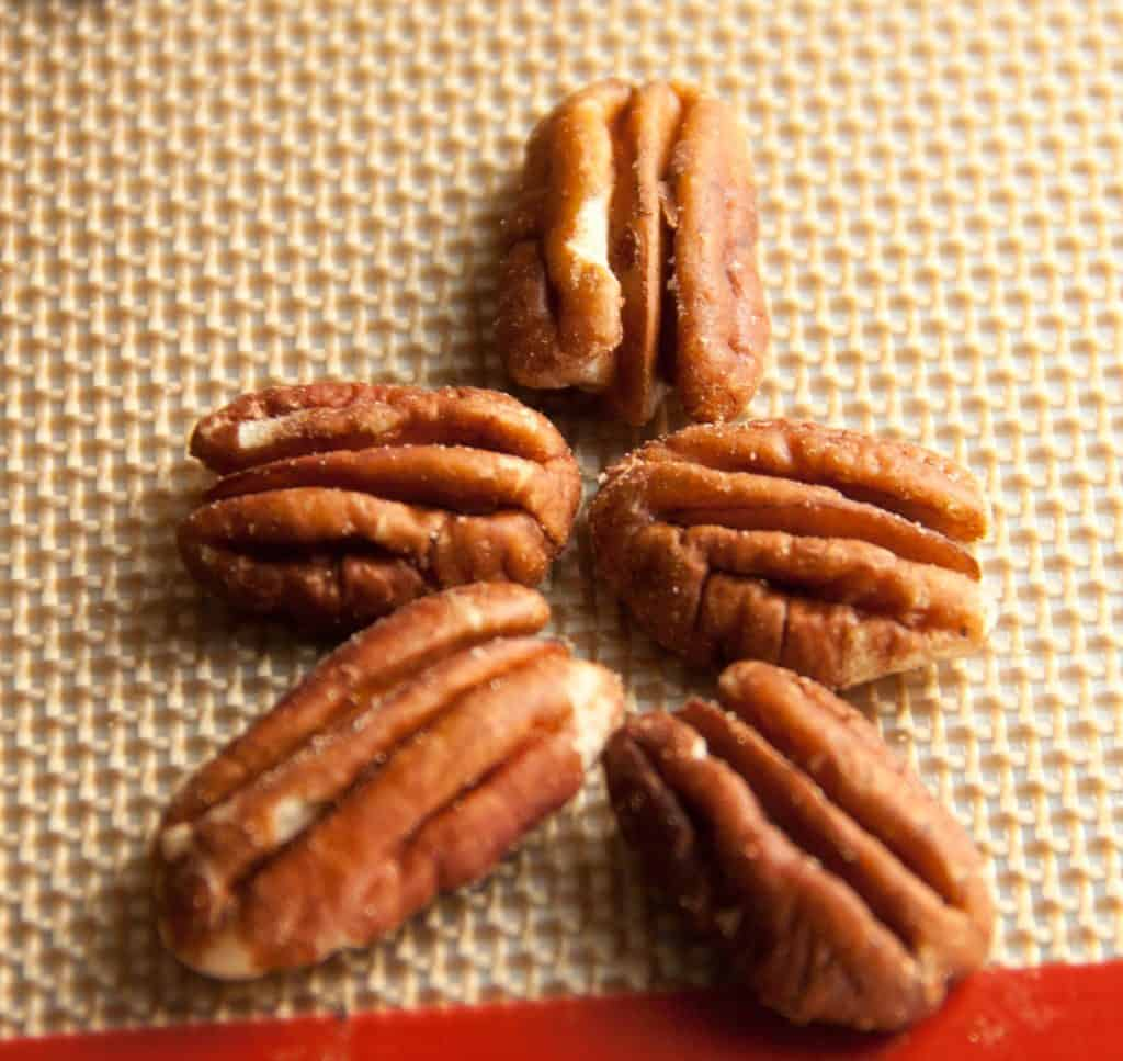 5 pecans for homemade turtles arranged in a star shape on baking mat
