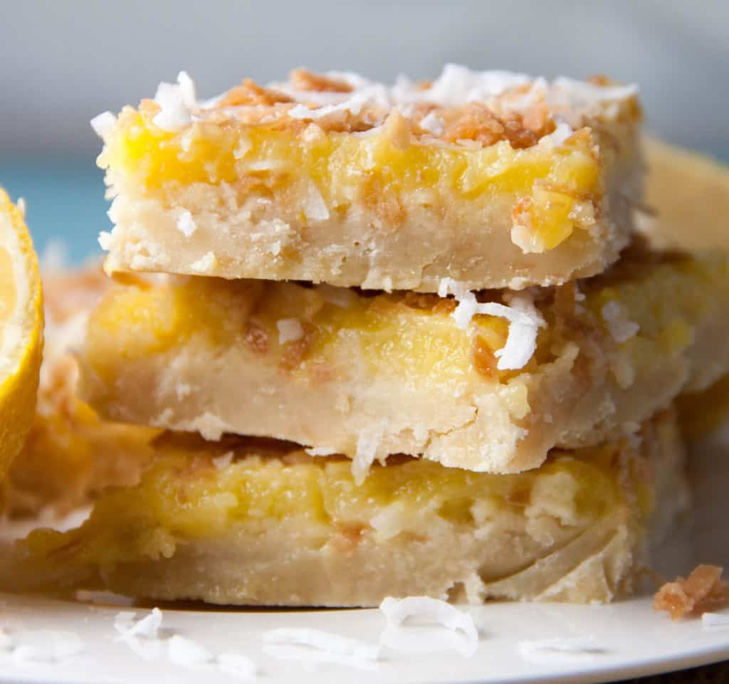 three Coconut Lemon Bars stacked on top of each other