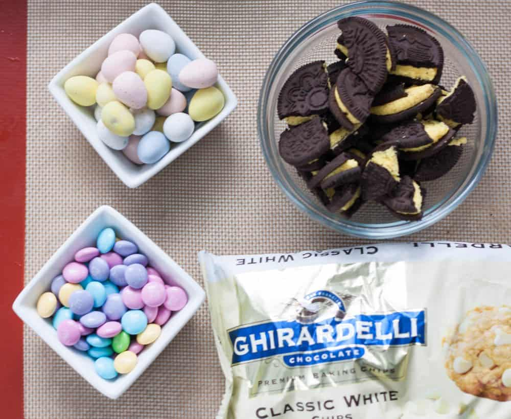 dish of cadbury mini eggs, M&M's, Oreos, and a bag of white chocolate chips