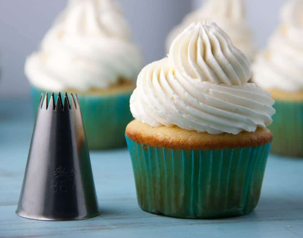 Metal piping tip  next to a vanilla cupcake in a green cupcake liner