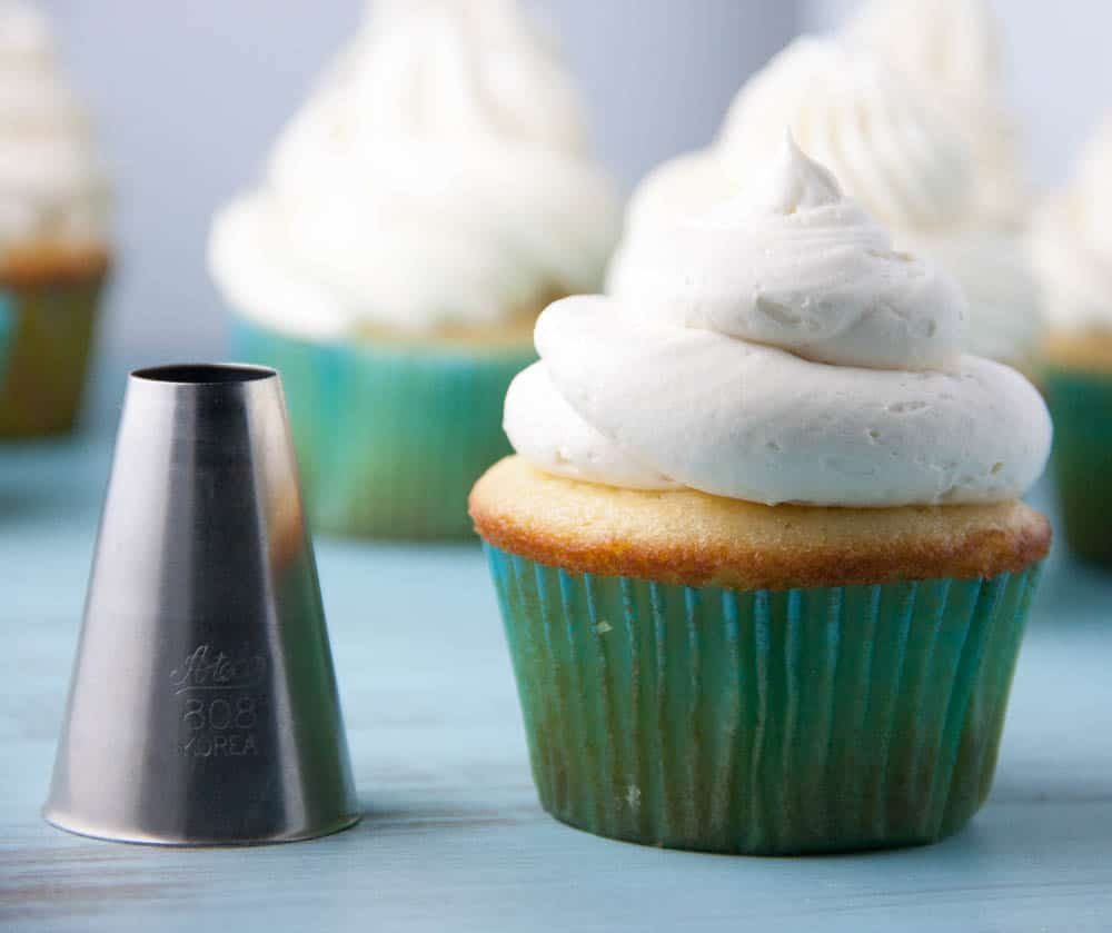 round piping tip next to a vanilla cupcake in a green cupcake liner