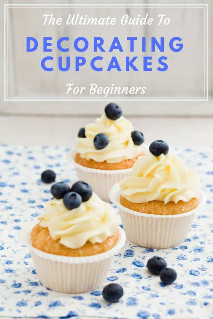 three vanilla cupcakes topped with blueberries and the photo is titled the ultimate guide to decorating cupcakes for beginners