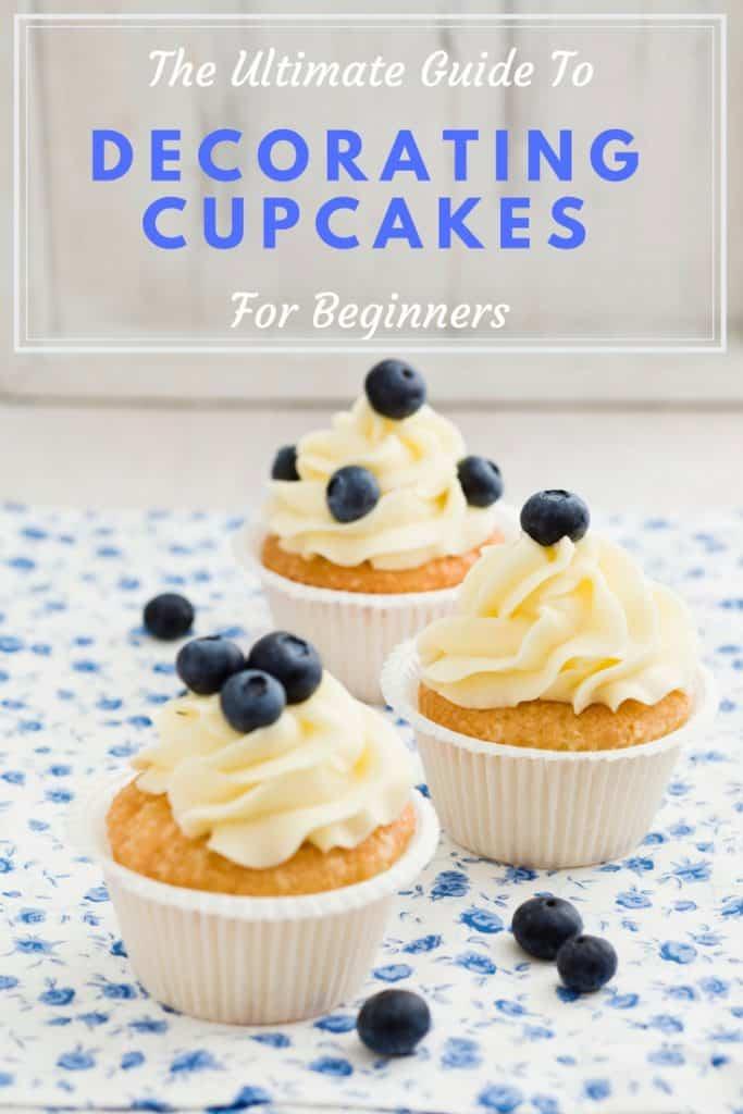 três cupcakes de baunilha cobertos com mirtilos e a fotografia intitula-se o derradeiro guia para decorar os seus cupcakes para principiantes