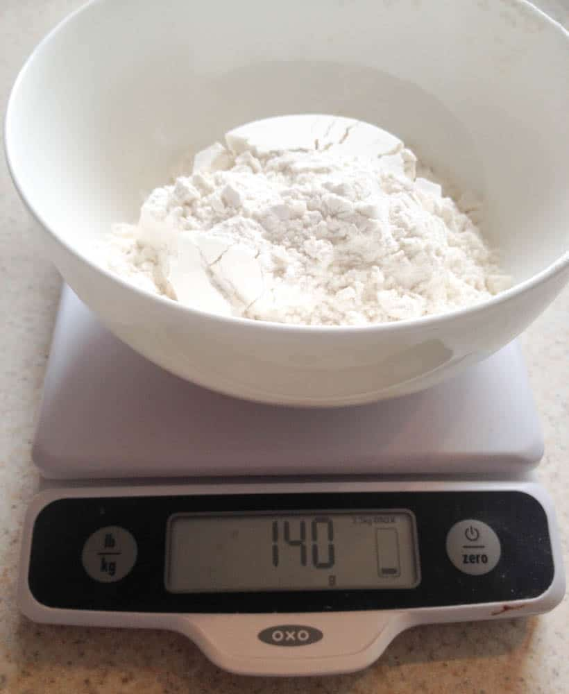 a bowl of flour on a kitchen scale