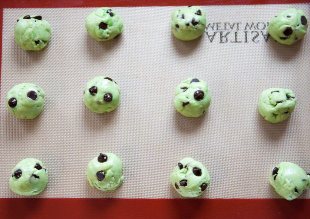 Mint Green cookie dough balls with chocolate chips on a cookie sheet