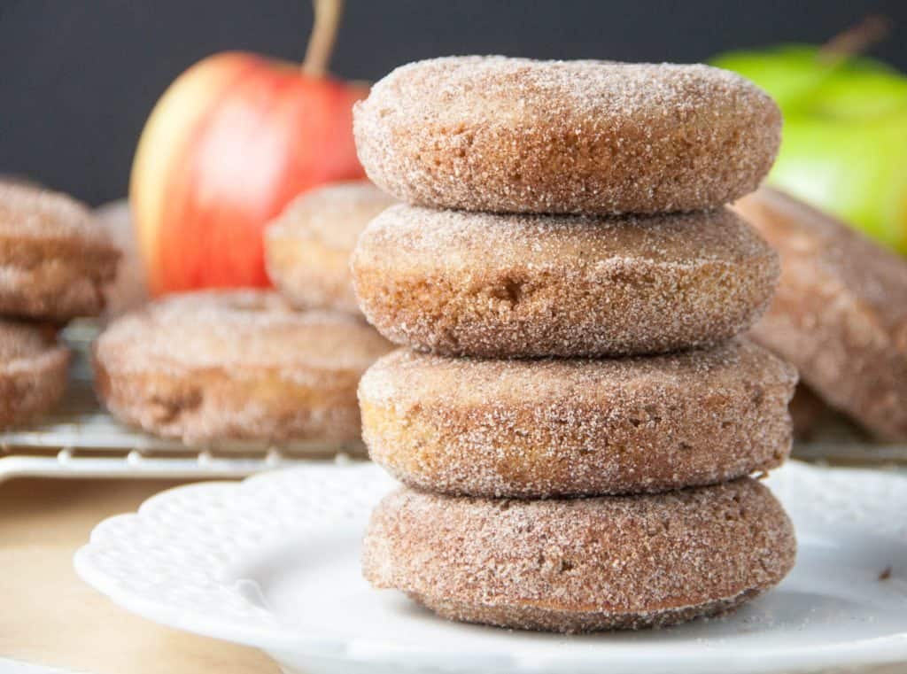 four apple cider donuts stacked on a plate