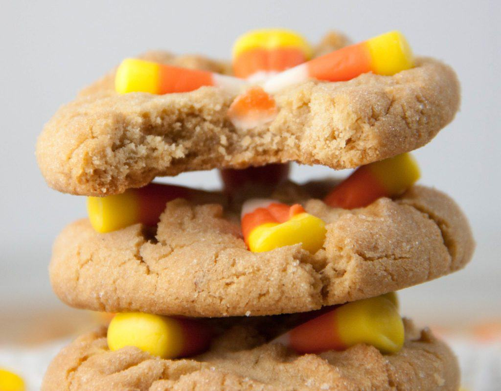 candy corn cookie stacked with top one with a bite taken out of it