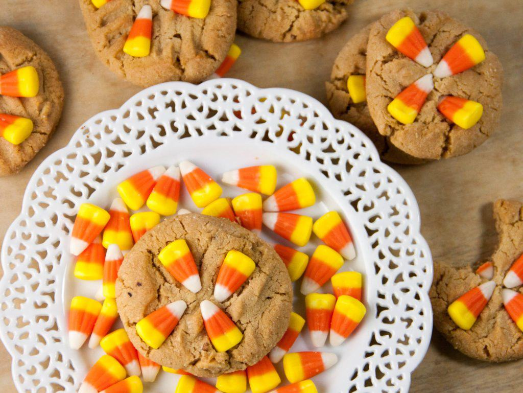 peanut butter cookie topped with candy corn on a plate with more candy corn