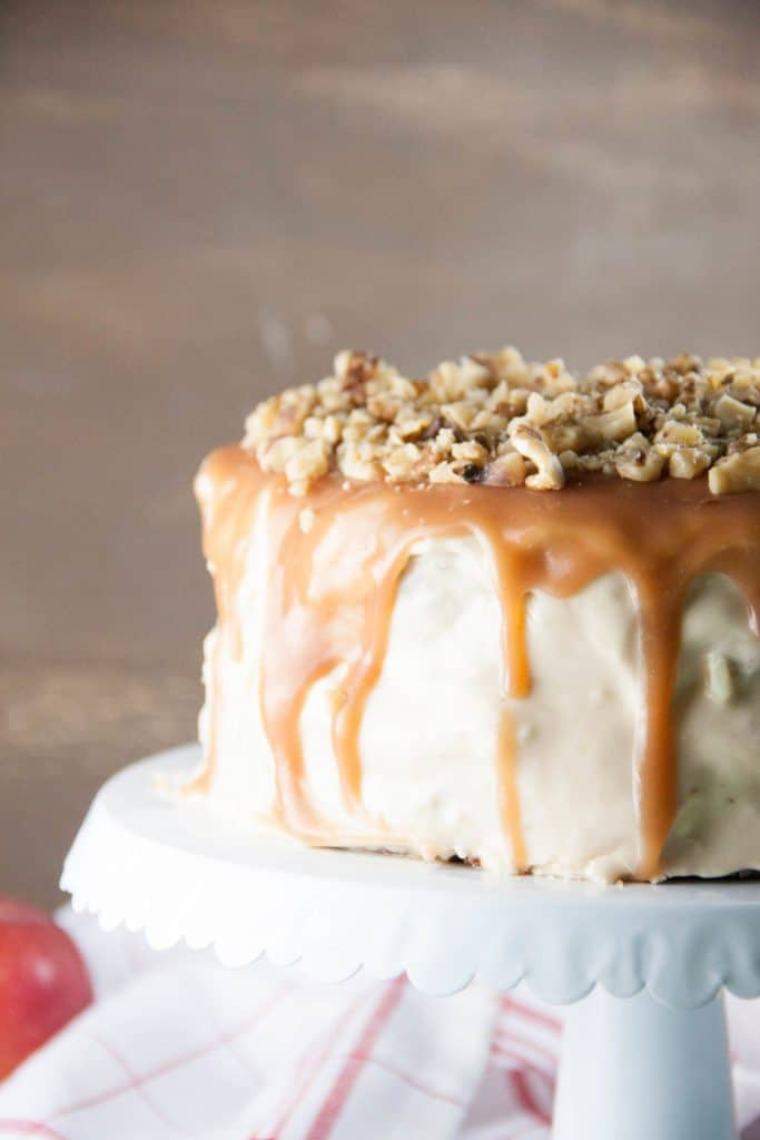 salted caramel apple cake topped with walnuts on a cake stand