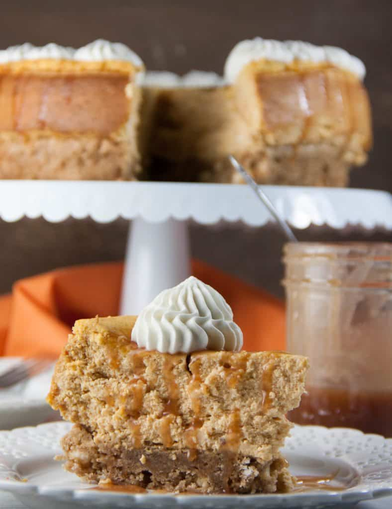 pumpkin blondie cheesecake slice with whole cheesecake in background