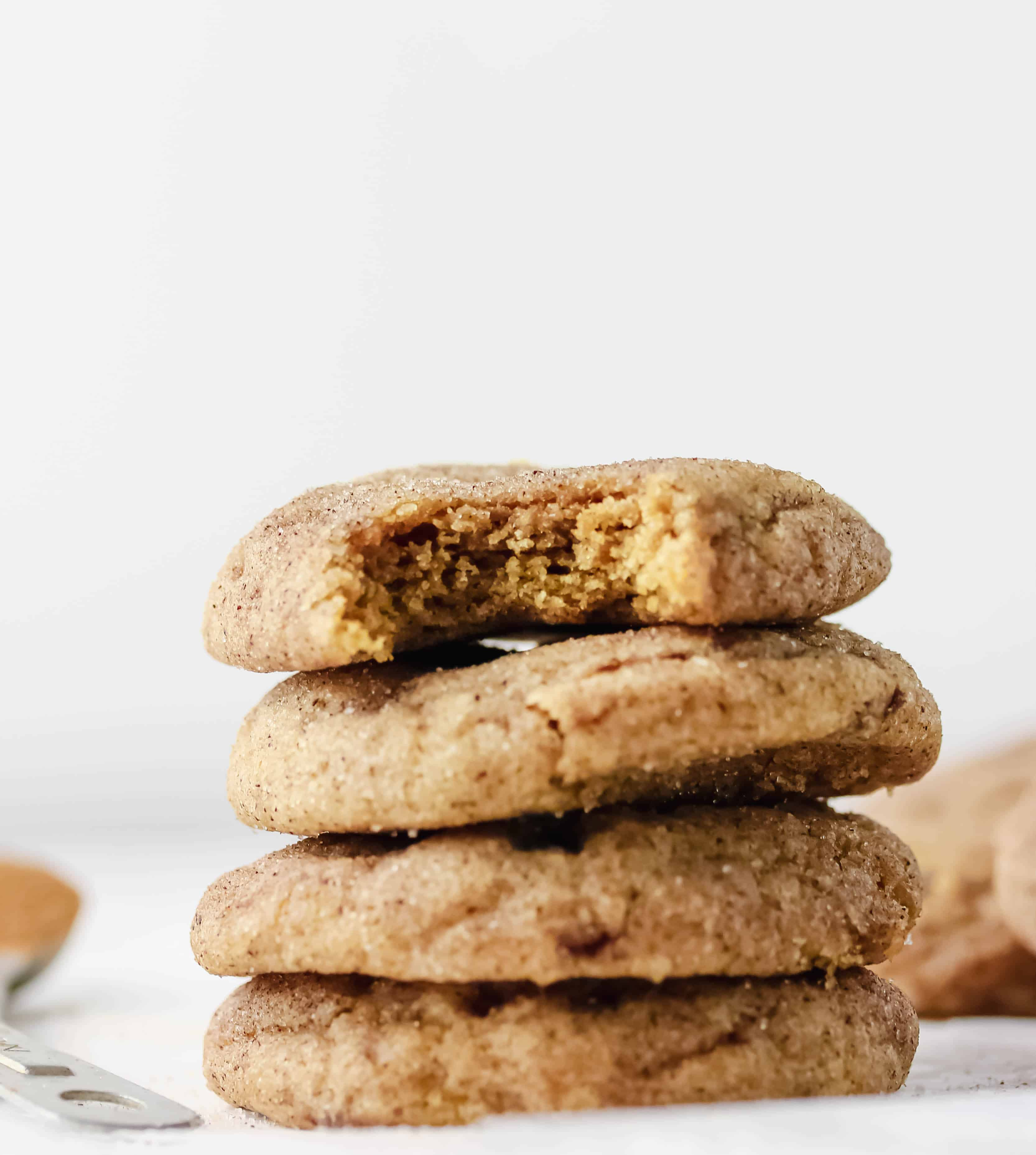 stack of pumpkin cookies with a bite taken out of the top one
