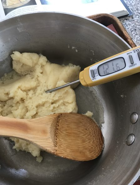 digital thermometer inserted into cream puff pastry