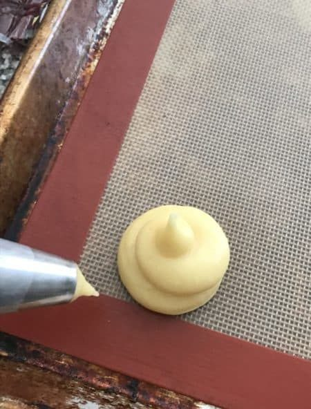 cream puff piped onto cookie sheet