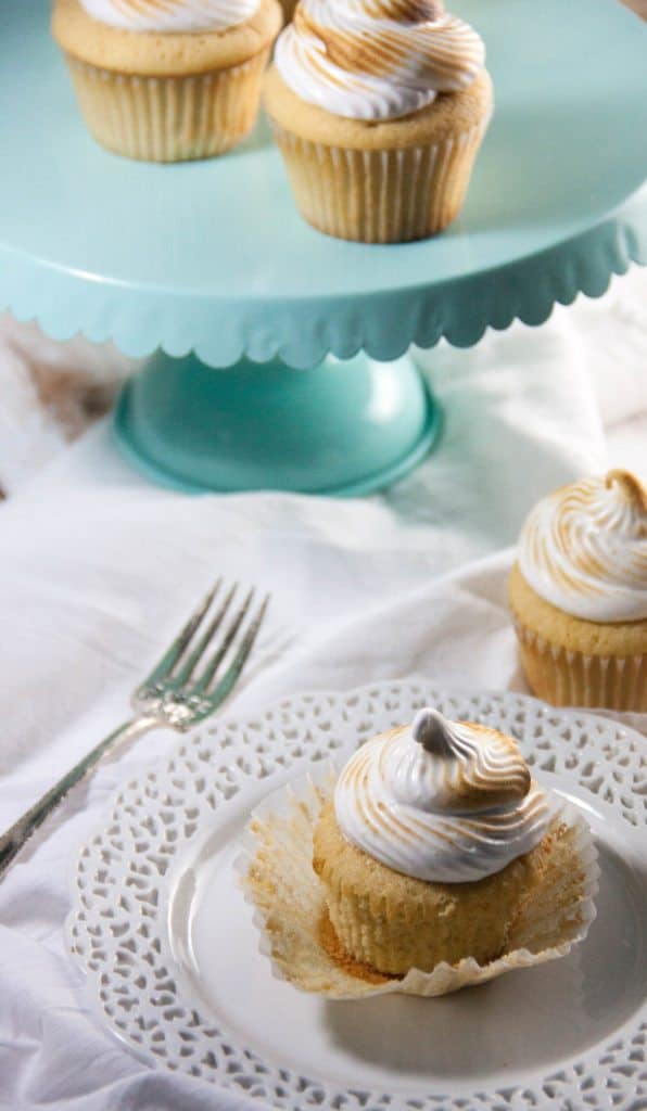 cupcake on a plate with a fork and cupcakes on a cake stand