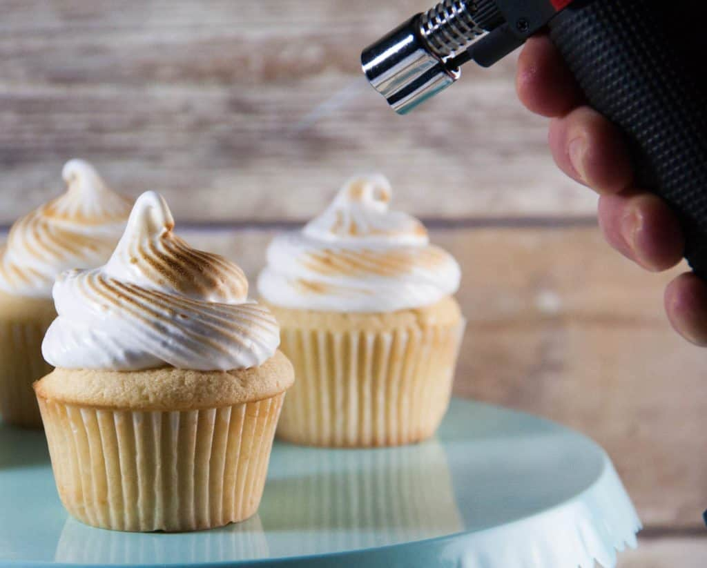 kitchen torch toasting meringue frosting on a cupcake