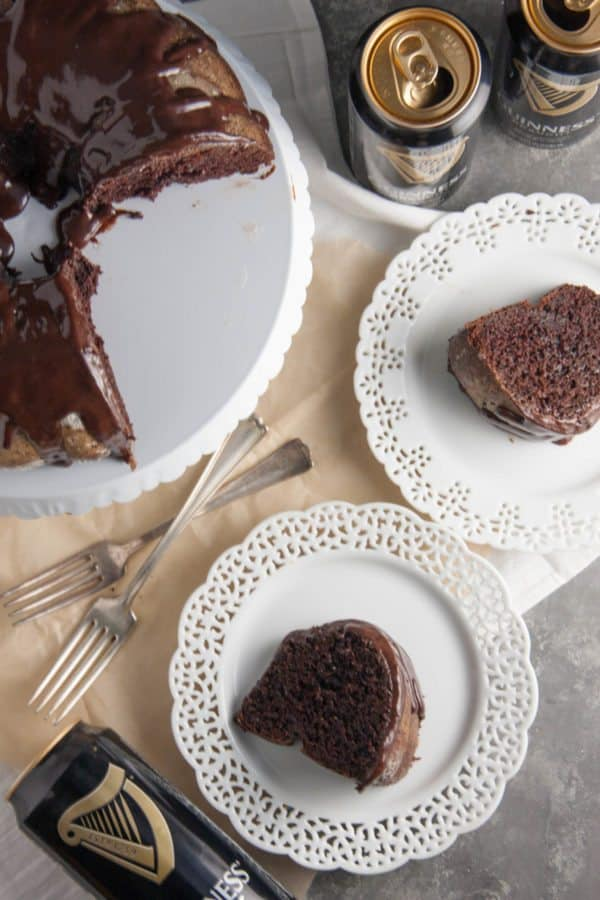 Dark Chocolate Guinness Cake slices on plate, guinness cans, and whole cake on cake stand