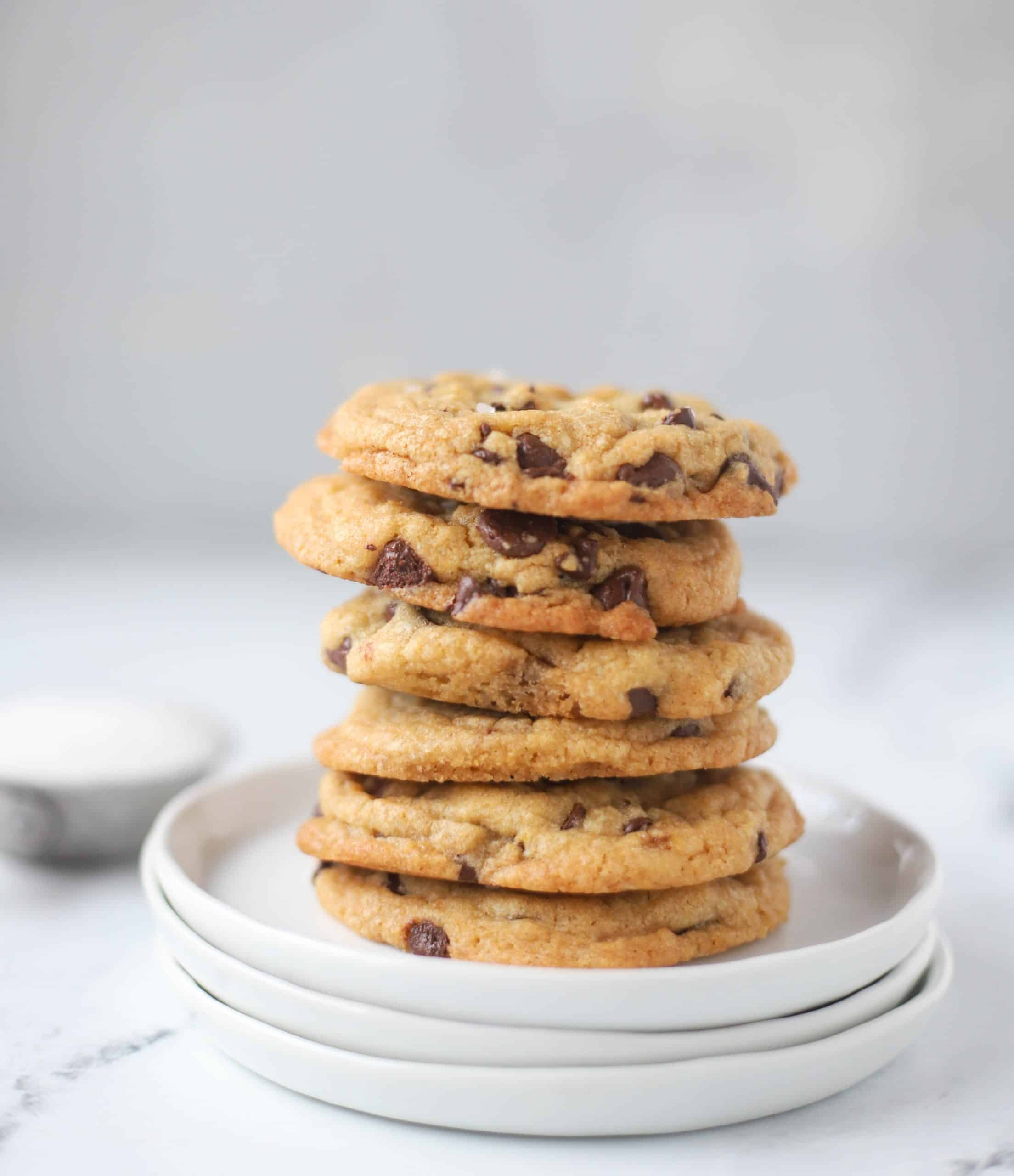 six browned butter chocolate chip cookies stacked on a plate