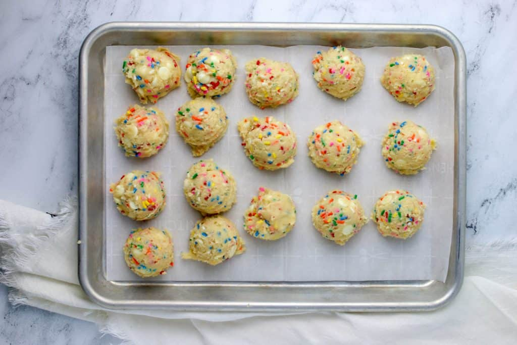 funfetti cookie dough scooped onto parchment paper cookie sheet