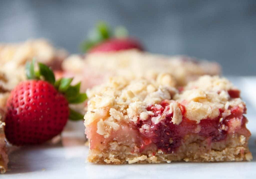 strawberry rhubarb bar next to a strawberry