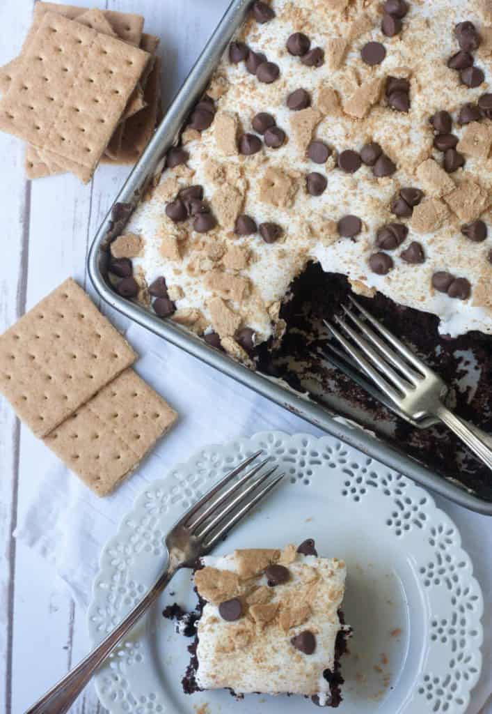 s'mores cake slice on a plate and cake in the pan next to it