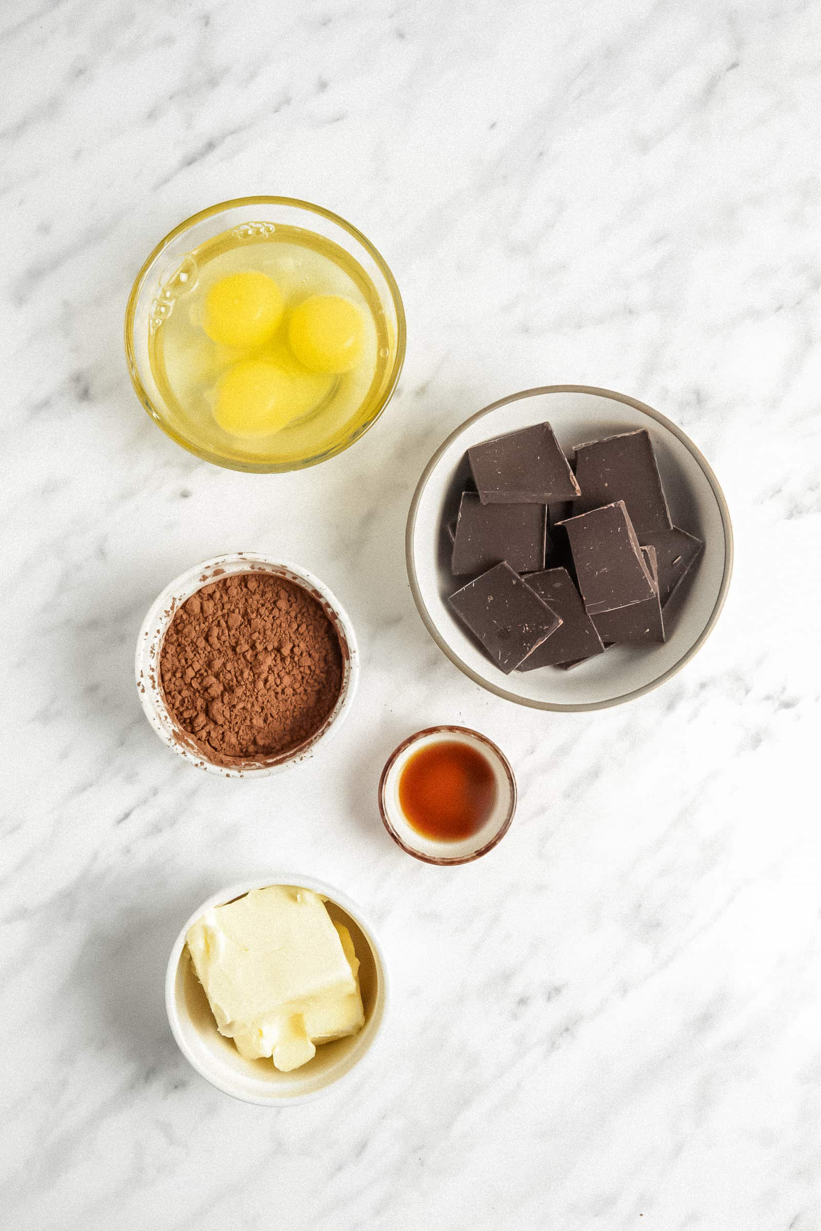 ingredients for flourless chocolate cake prepped in small bowls