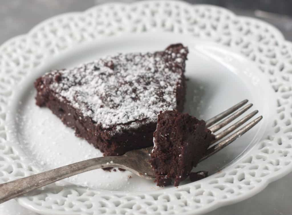 slice of flourless espresso cake on a plate with a fork