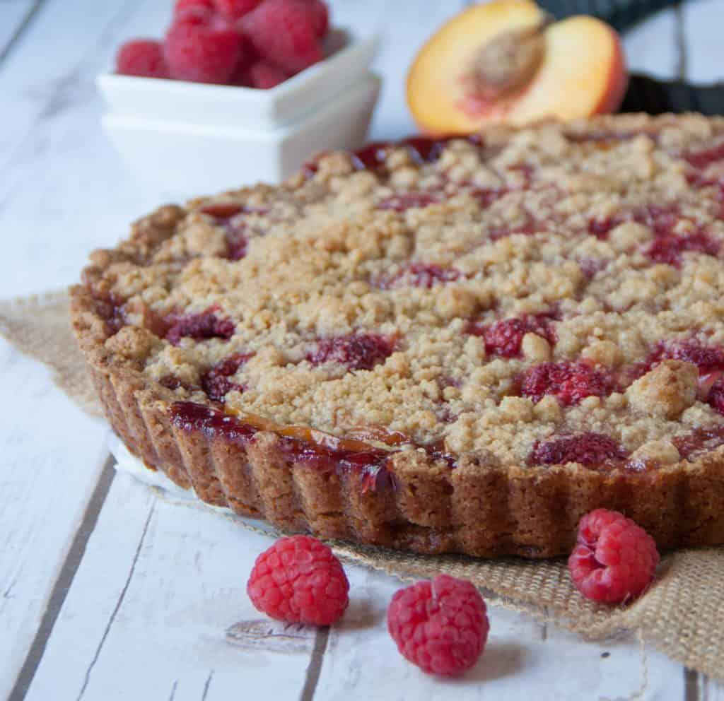 peach tart with a bowl of raspberries
