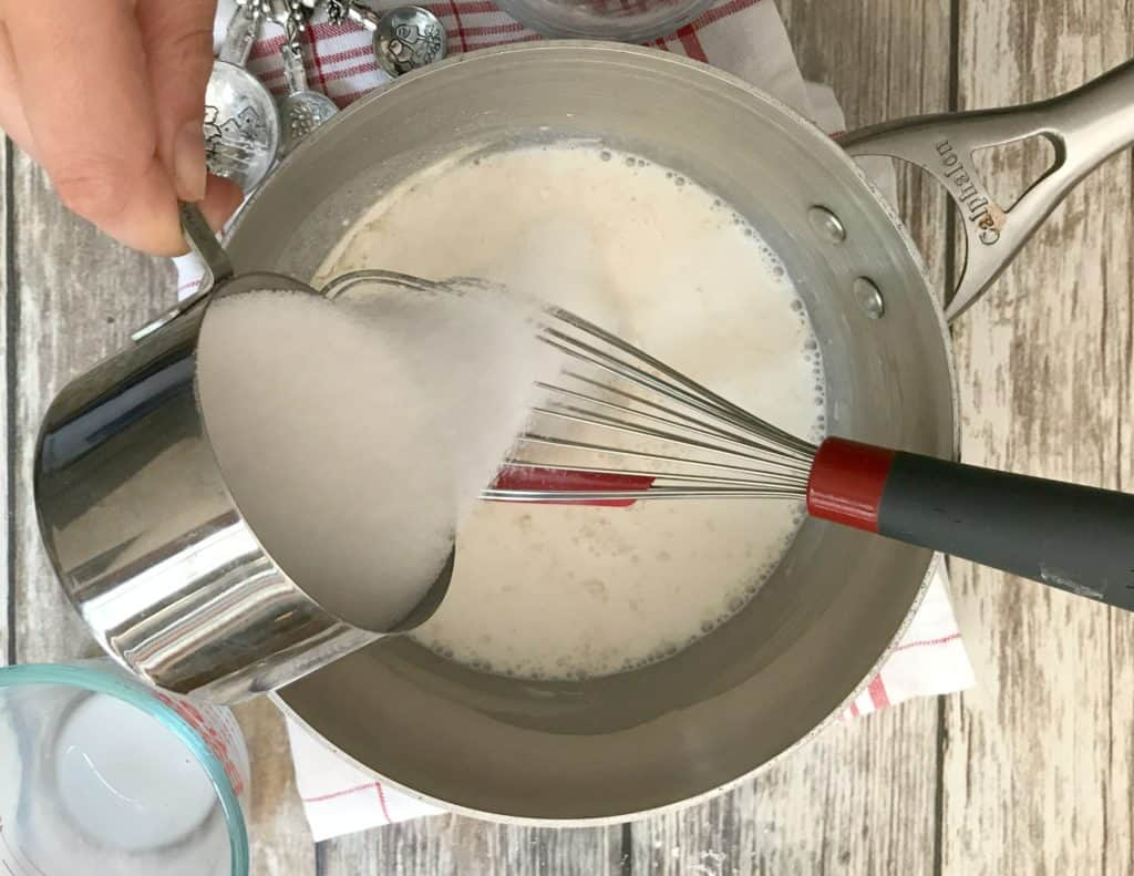 Sugar poured into milk that is in a pan with whisk