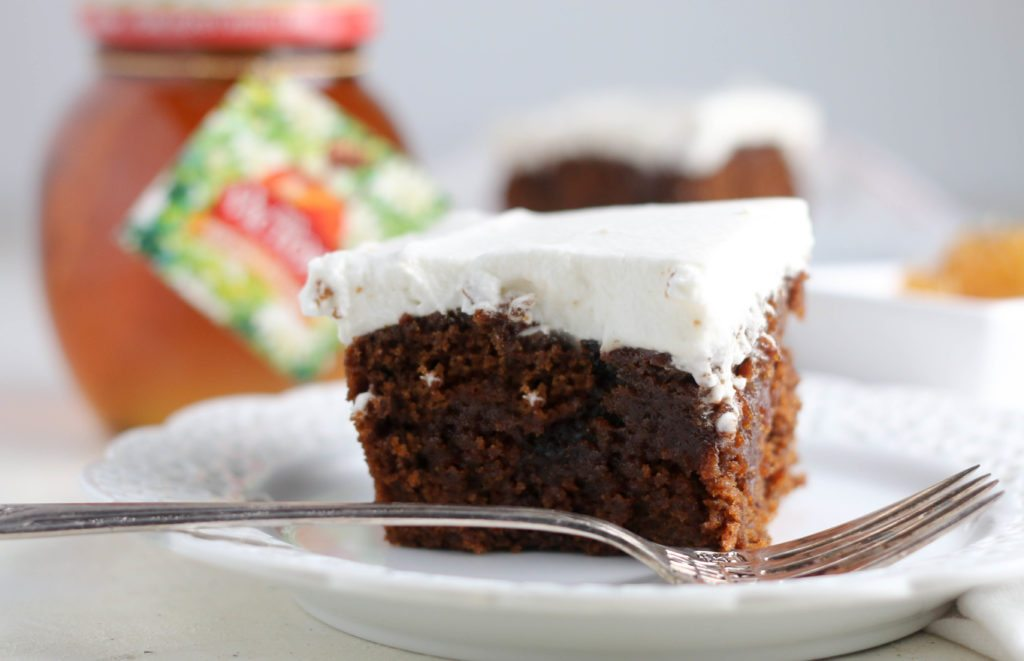 gingerbread poke cake slice on a plate with a fork
